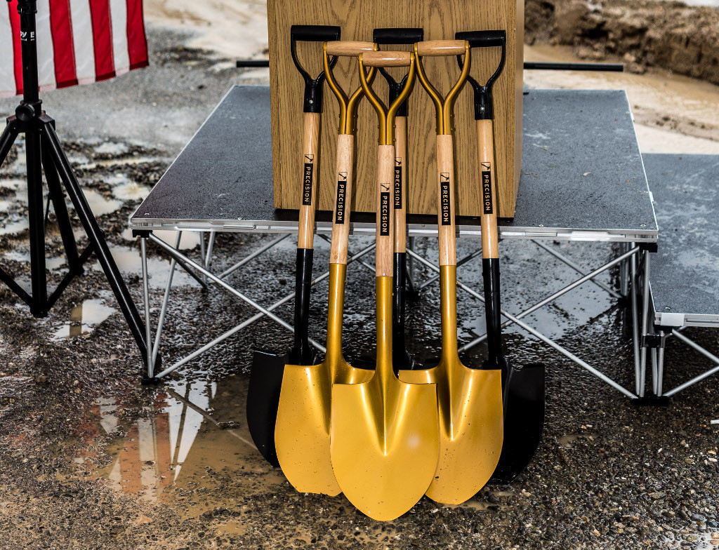 Three gold shovels and three black shovels leaning against a podium at the Rocky Hill Groundbreaking Ceremony