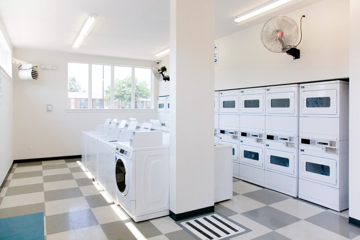 Laundry room with white washers and dryers at the Coventry Gardens Community Building
