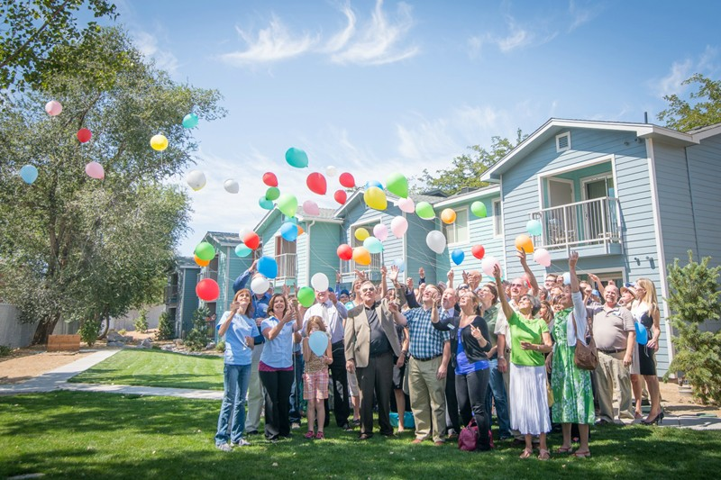 Happy residents at Indigo Village release balloons into the air