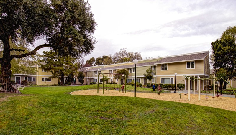 Green grass, play ground, trees and buildings at Los Robles apartments