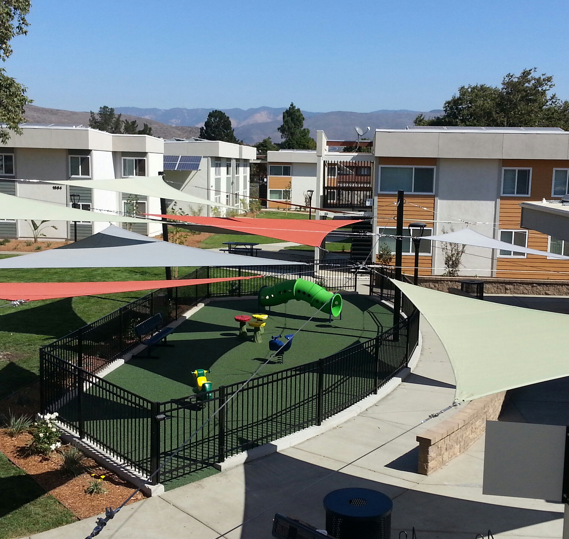 Fenced play area, awnings, and walkways at Madonna Road Apartments